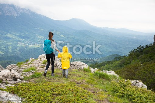 A young woman and a boy are holding hands while hiking in the mountains with a magnificent view