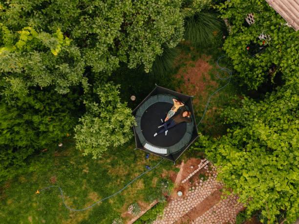 junge und seine mutter auf einem trampolin - gartentrampolin stock-fotos und bilder