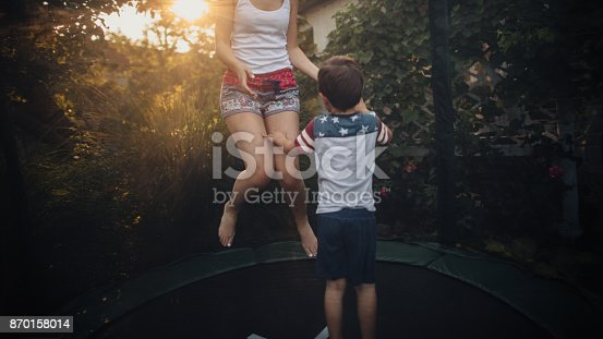 Photo of cute, smiling, little boy jumping on a trampoline with his mother // wide photo dimensions