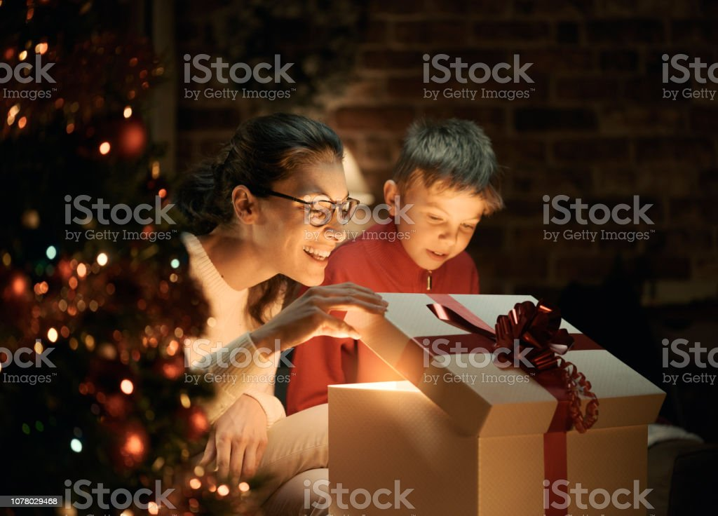 Boy and his mother opening Christmas gifts stock photo