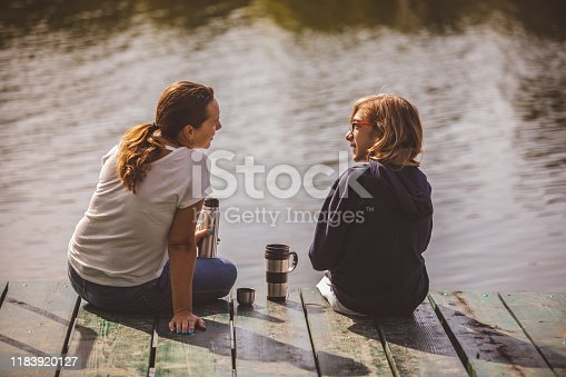 Mother and son sitting on a pier in the sunlight