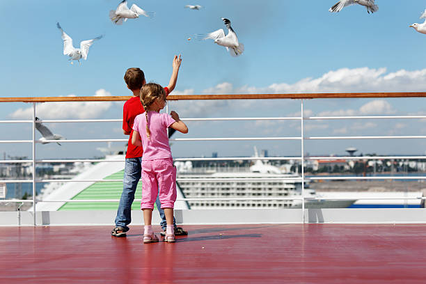 Boy and his sister feed seaguls on deck of ship. stock photo