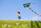 Child flying a kite with blue sky in background