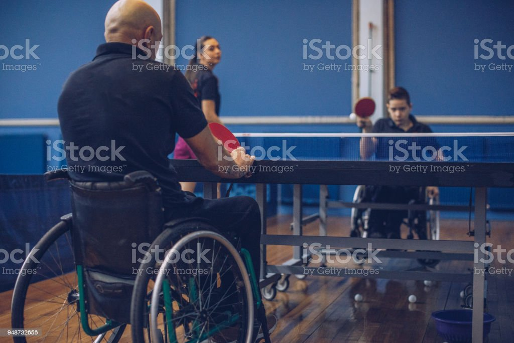 Boy and man playing table tennis stock photo