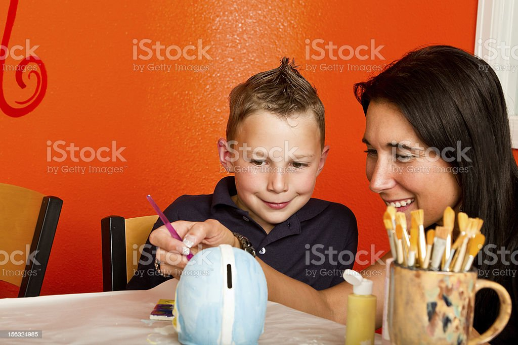 Boy and Mom Painting Pottery stock photo