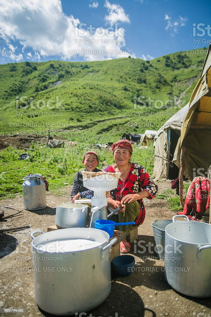 NARYN, KYRGYZSTAN-JULY 20 2016 Boy and mother making butter stock photo