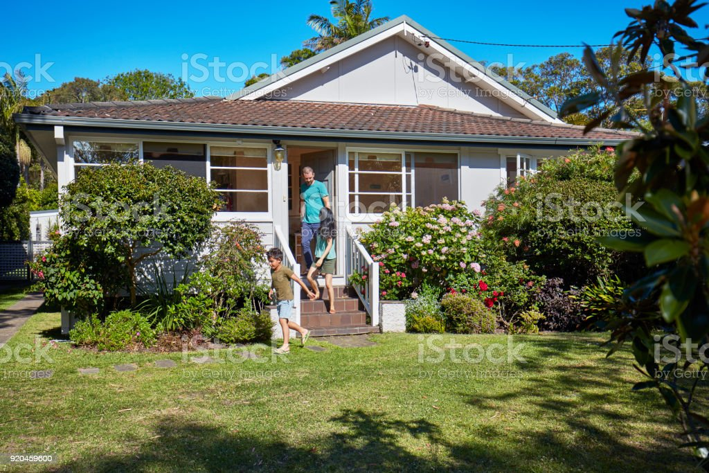 Boy and parents coming out of house stock photo