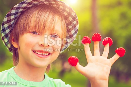 Boy with raspberry on his fingers