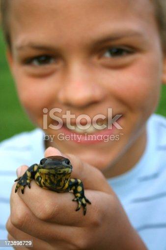 A boy proudly showing off his pet salamander.