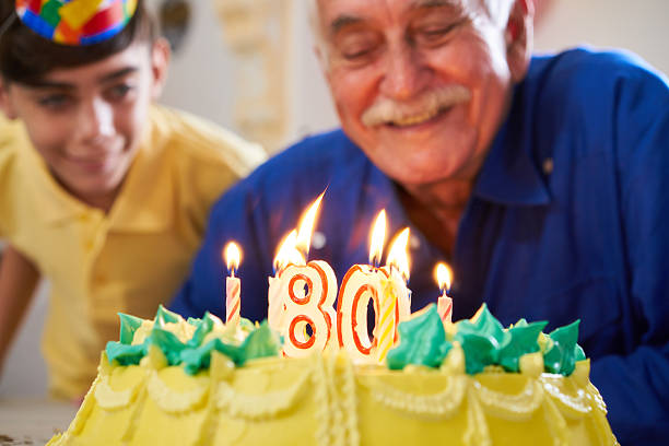 Boy and Senior Man Blowing Candles On Cake Birthday Party stock photo