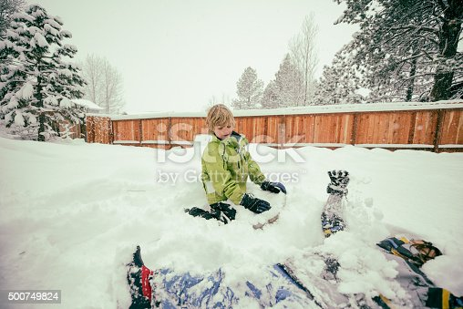 865399512istockphoto Boy and sister playing in snow in backyard 500749824