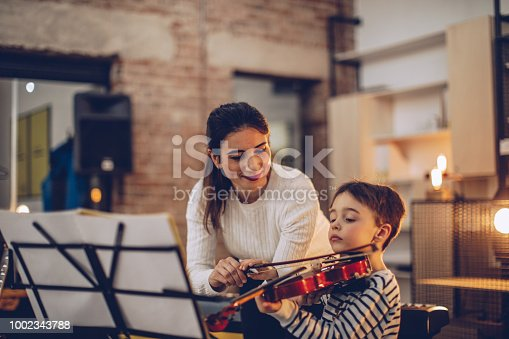 Two people, woman violin teacher working with little boy on violin lessons.