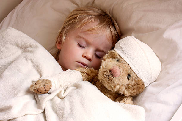 boy and teddybear in bed - head injury stock photos and pictures