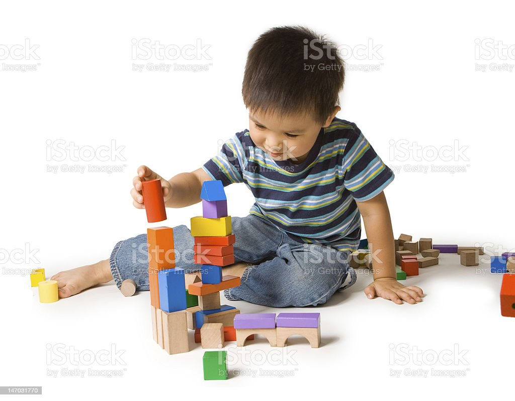 Boy and tower of colorful wooden building blocks stock photo