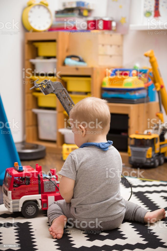 Boy and Toy Fire Truck - A toddler playing with a toy fire truck in...
