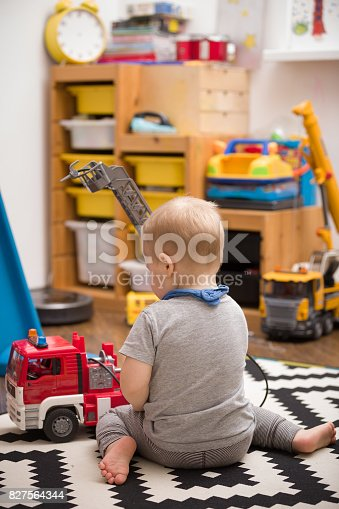 184659330 istock photo Boy and Toy Fire Truck  - A toddler playing with a toy fire truck in childroom. A blond little child playing cars in kid's room. Leisure activities. Playground. indoors. Profession. Fireman. 827564344