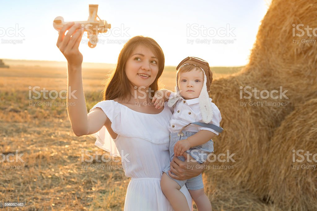 Boy and woman playing in aviator hat in the field. royalty-free stock photo