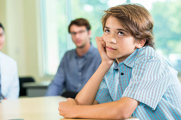 Boy annoyed with parents Boy rolling his eyes at his parents. He is turned away from them. rolling eyes stock pictures, royalty-free photos & images