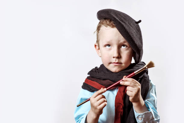 boy artist in black beret and paint brush in hand on a light background stock photo