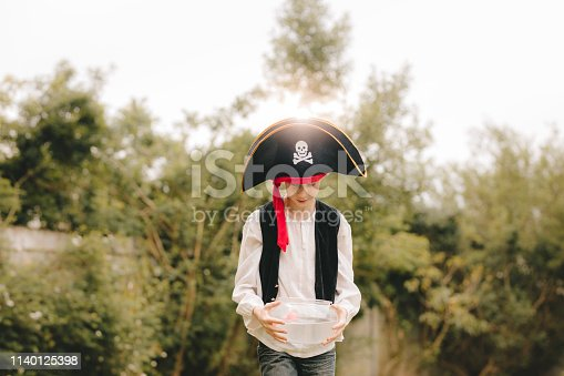 109350576 istock photo Boy as a pirates walking with fish bowl 1140125398