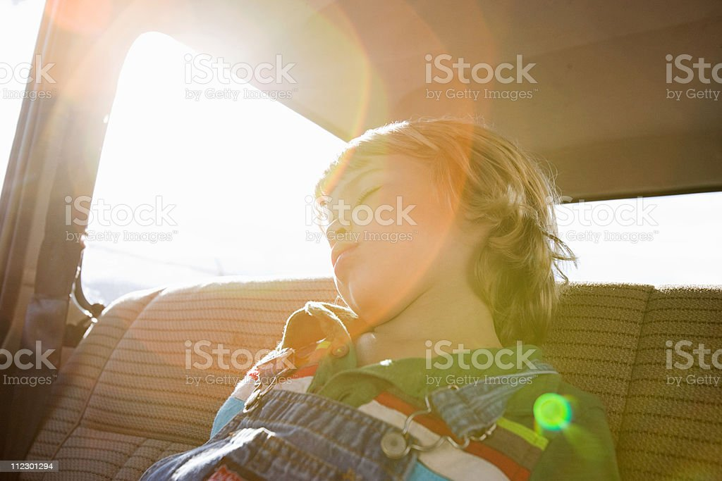 Boy asleep in back seat of car stock photo