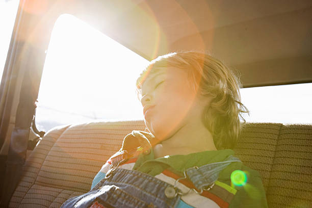 Boy asleep in back seat of car  bib overalls boy stock pictures, royalty-free photos & images