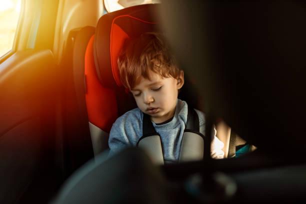 garçon dormant dans le siège arrière de la voiture - child car sleep photos et images de collection