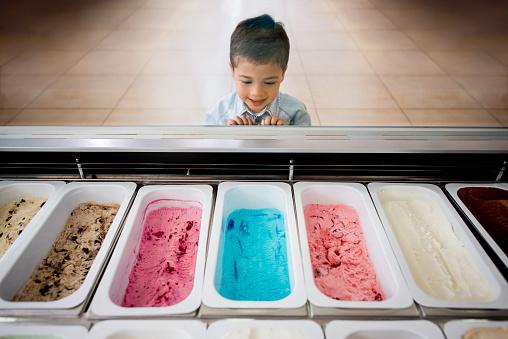 Beautiful Latin American boy at an ice cream shop choosing a flavor