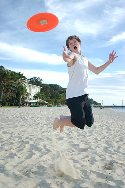 Boy at Beach Jumping to Catch a Flying Frisbee stock photo