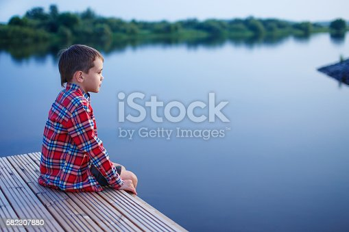 pensive boy in a plaid shirt sitting on a wooden pier near the water. side view. empty space for your text