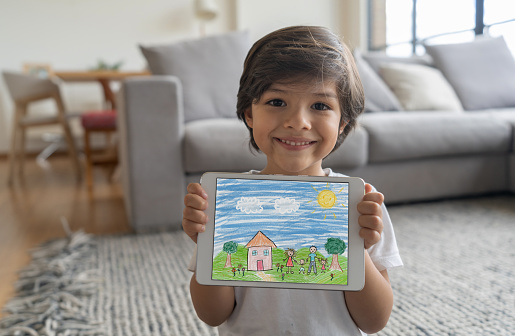 Happy boy at home showing a drawing he made on a tablet computer and looking at the camera smiling - lifestyle during lockdown concepts