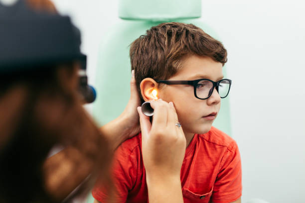 Boy at medical ears examination Young boy at medical examination or checkup in otolaryngologist's office infectious disease stock pictures, royalty-free photos & images