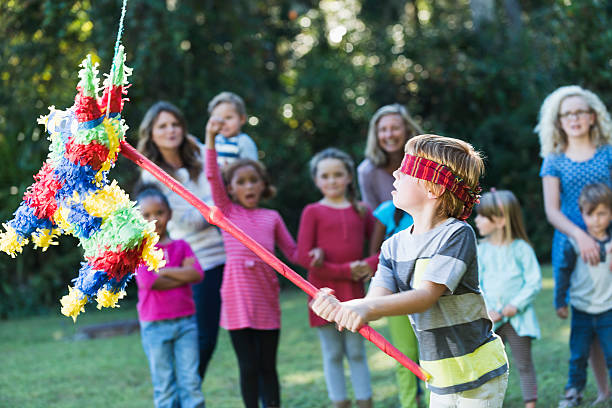 boy at party hitting pinata with stick - cinco de mayo party stock photos and pictures