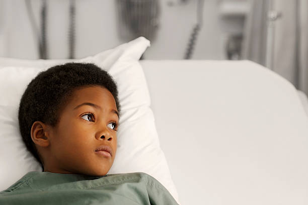 Boy at the hospital in bed stock photo