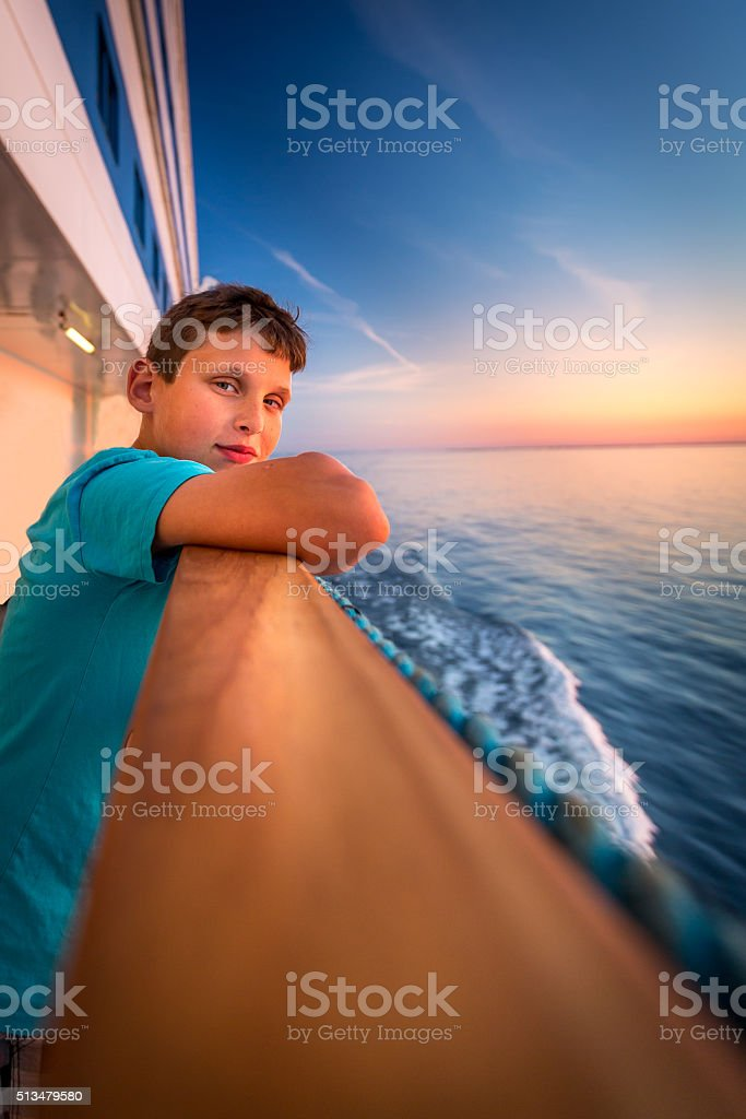 Boy at the railing of a cruise ship at sunset. royalty-free stock photo