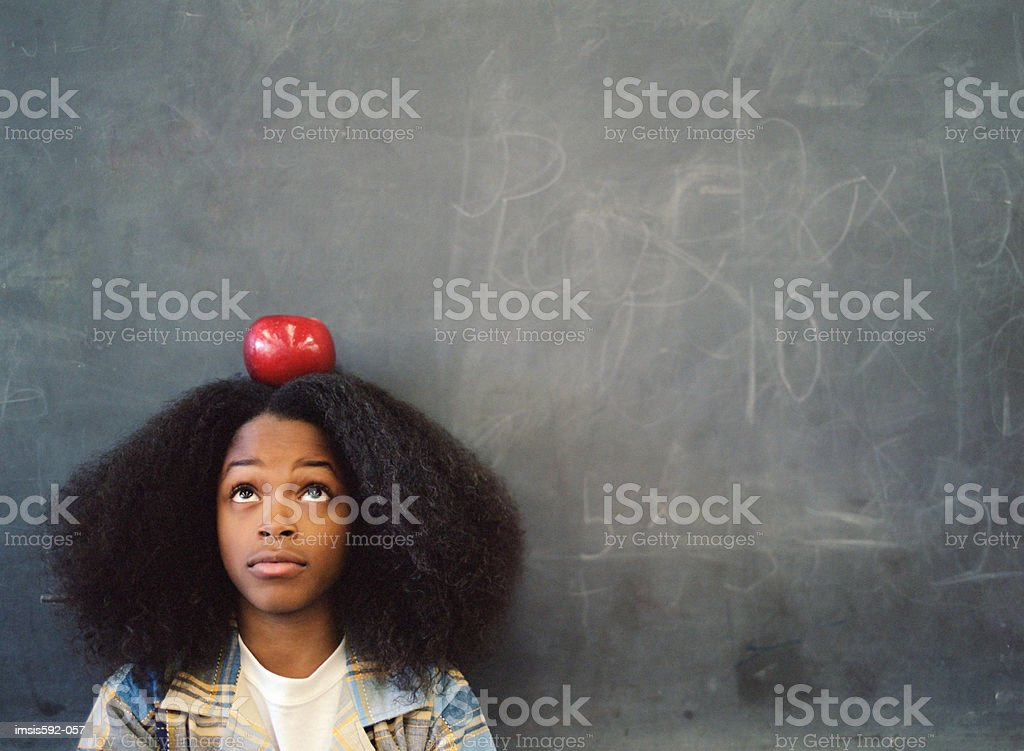 Boy balancing an apple on his head royalty free stockfoto