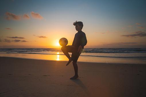 Boy balancing ball on knee at sunrise