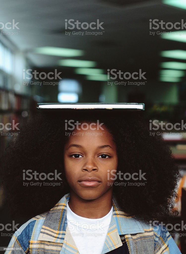 Boy balancing book on head royalty-free stock photo