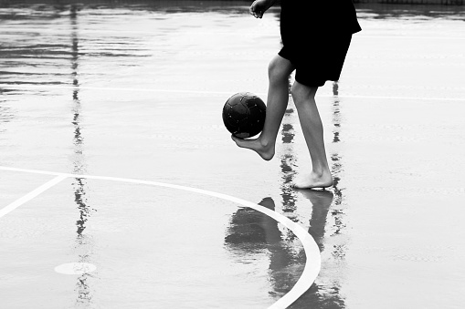 Boy barefoot playing soccer in the rain.
