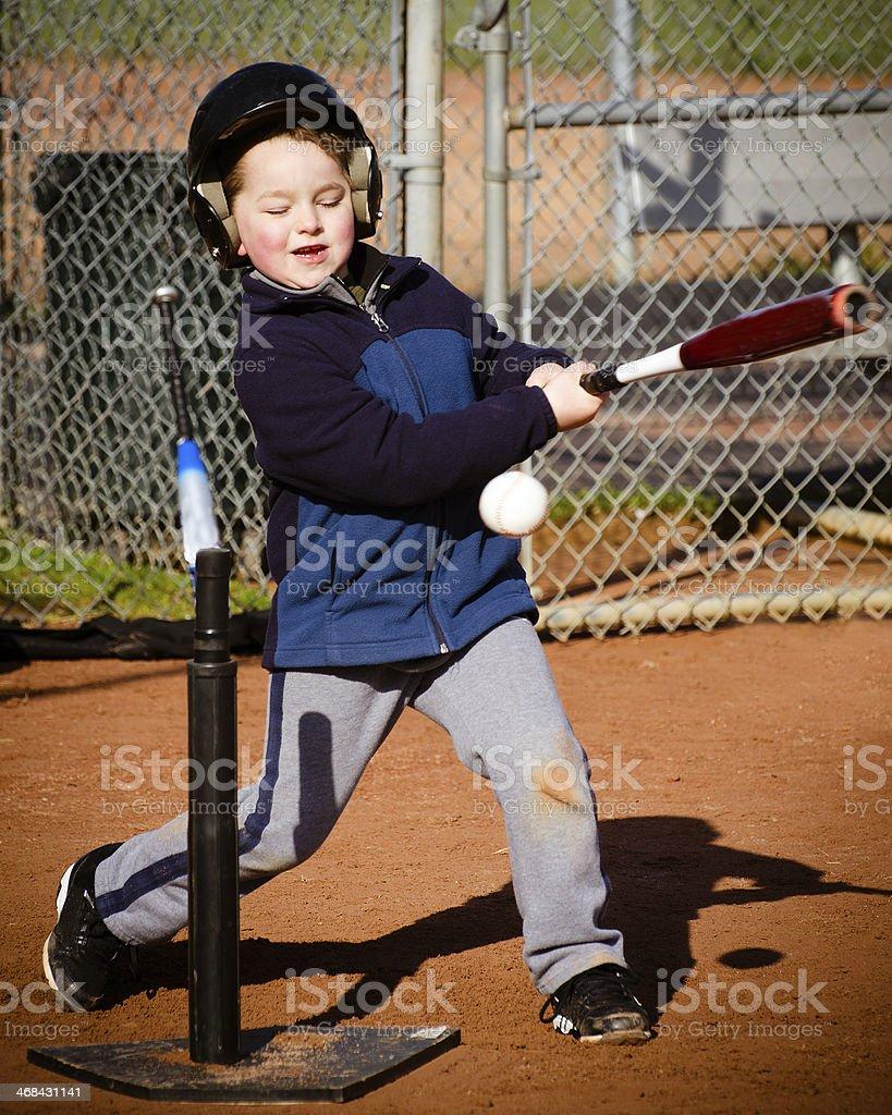 Boy batting at T-ball practice stock photo