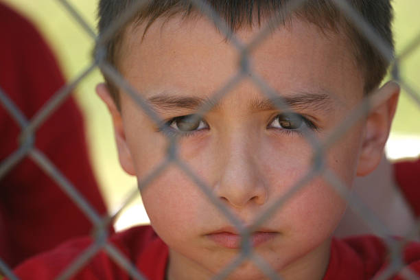 Boy behind fence stock photo