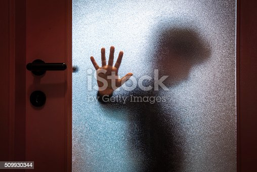 Blurred sad boy leaning open hand against glass door.