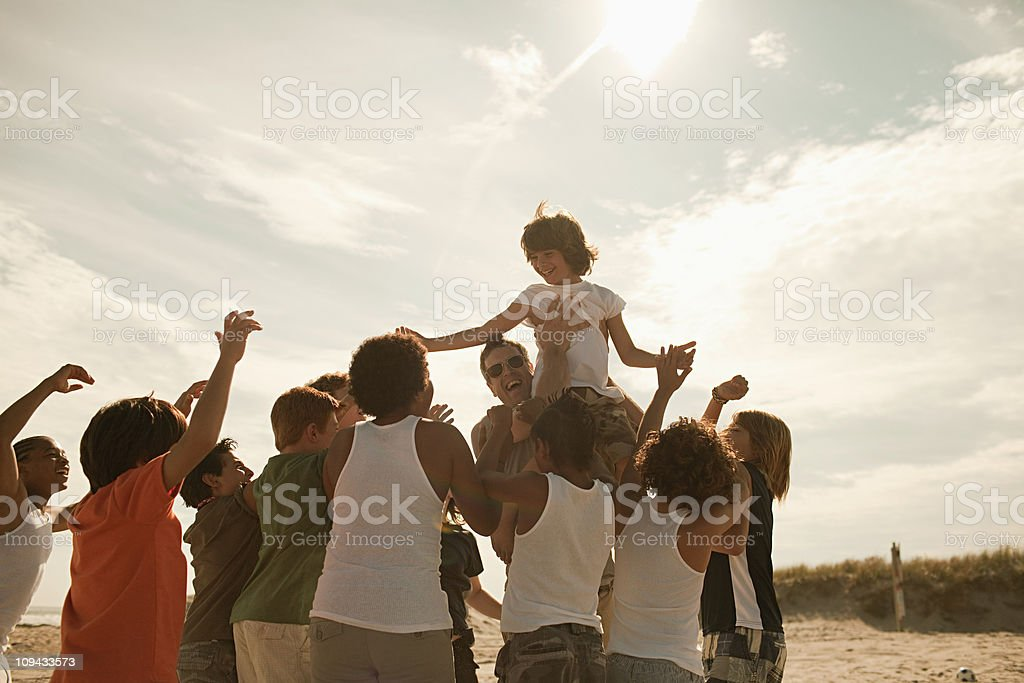 Boy being carried on shoulders stock photo