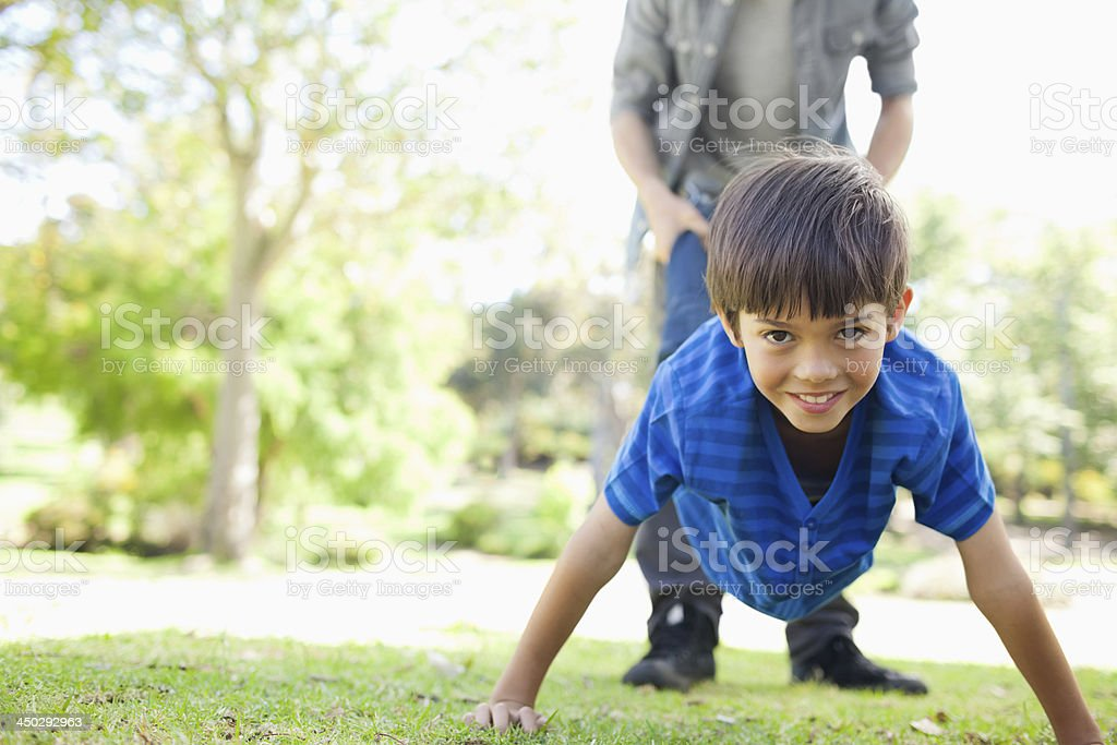 Boy being held up by his feet while smiling stock photo