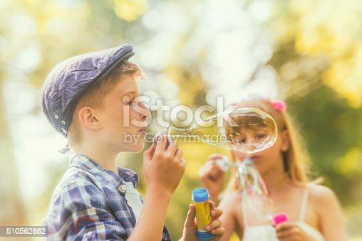 618034312 istock photo Boy blowing a soap sud with girl in the background 510562882