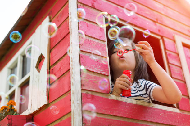 pojke blåser bubblor i en trä lekstuga - summer sweden bildbanksfoton och bilder