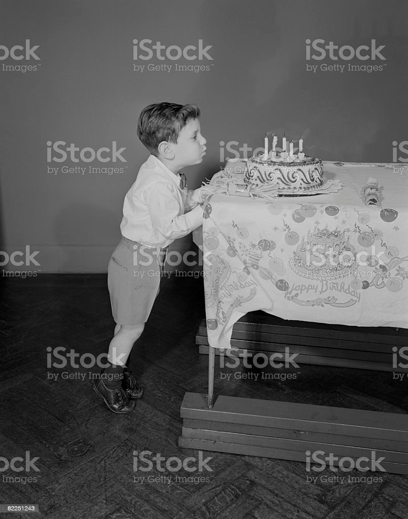 Boy (6-7) blowing candles on birthday cake stock photo