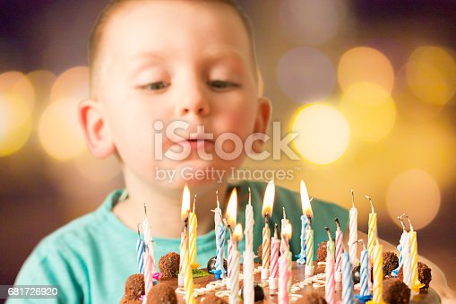 istock Boy Blowing on Birthday Cake with Candles 681726920