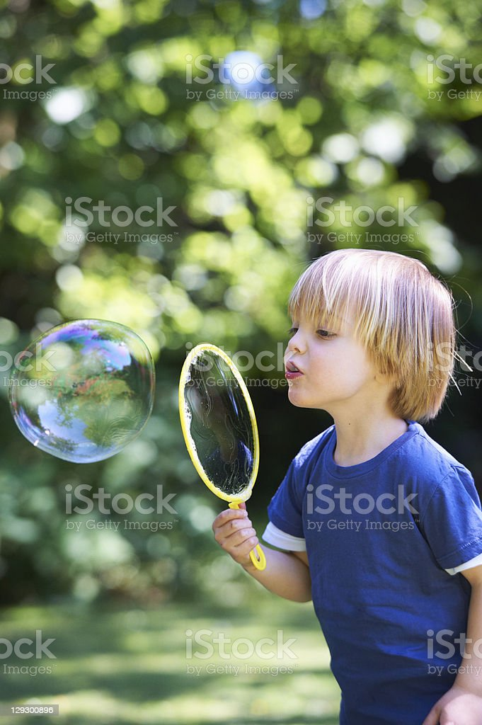 Boy blowing oversized bubble in backyard stock photo