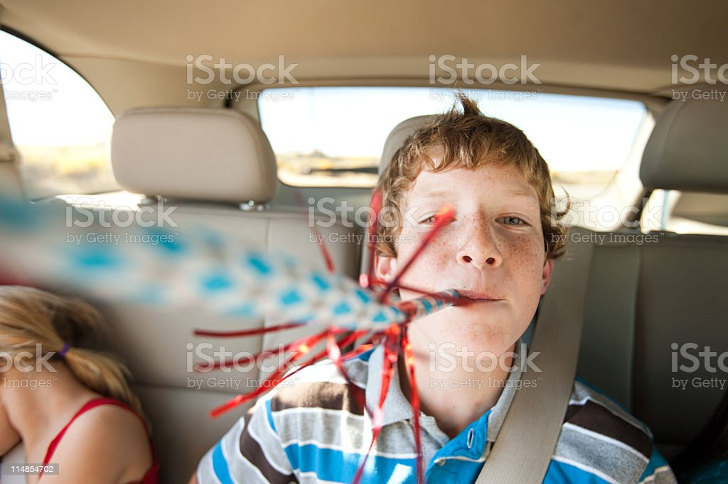 Boy blowing party blower in back seat of car stock photo